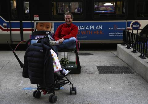 Lelio Ciciliani of Argentina smiles at his 7-month-old daughter Ignacia Ciciliani during a break in their walk. Ciciliani paused to sit on one of the many sets of ballpark seats set up on Michigan Avenue to commemorate the 100th anniversary of Wrigley Field.