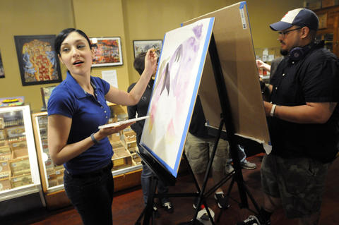 "Illustrator Chrissie Zullo, of New Haven, left, a guest artist at Hartford Comic Con, which is being held through June 1 at the XL Center in Hartford, turns to talk to a visitor at the Tobacco Shop on Pratt Street Friday night where she and fellow artist Christopher Uminga, also of New Haven, right, were making art to be displayed at the shop for the remainder of the show. She was doing a watercolor of ""Death,"" a character from the Sandman comic books."
