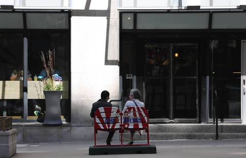 A couple sits in front of Starbucks in a set of painted baseball chairs on Michigan Avenue. The ballpark seats commemorate the 100th anniversary of Wrigley Field.