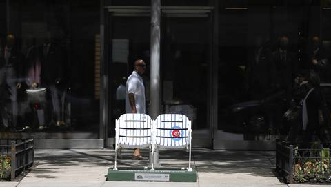 Pedestrians walk by an empty set of painted ballpark seats on Michigan Avenue to commemorate the 100th anniversary of Wrigley Field.