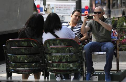Paul Rostam, left, and his friend Dave Matheson take a picture of women sitting across them in painted ballpark seats on Michigan Avenue. The chairs were placed to commemorate the 100th anniversary of Wrigley Field.