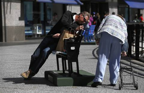 Henry Atsma, of Michigan, and a woman look at the numbers on the back of a set of painted ballpark seats on Michigan Avenue near the Hancock building that were placed to commemorate the 100th anniversary of Wrigley Field.