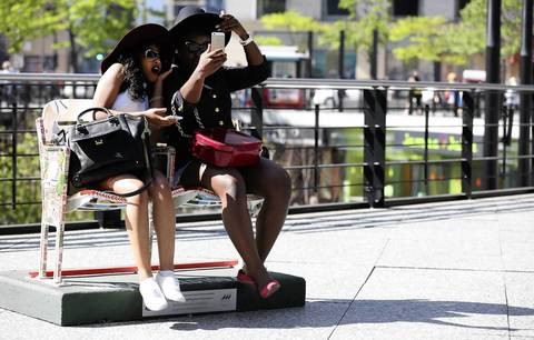 Meseret Muluken, left, and Delphine Vakunta, of Madison, Wisconsin take pictures of each other in one of the sets of painted ballpark seats on Michigan Avenue that commemorate the 100th anniversary of Wrigley Field.