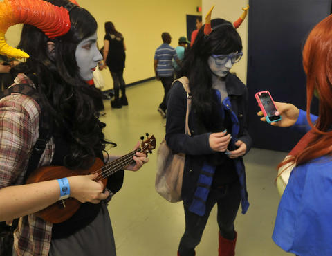 Xan Ellis of Windsor, left, and Margot Gagnon of Glastonbury, center, attend Hartford Comic Con at the XL Center Saturday.