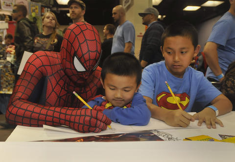 "Spiderman demonstrates a drawing for Kayden Ngov, 6, and Jonathan Ngov, 11, at a ""create-your-own comic strip"" table at Hartford Comic Con at the XL Center Saturday. Kayden and Jonathan are from Glastonbury."