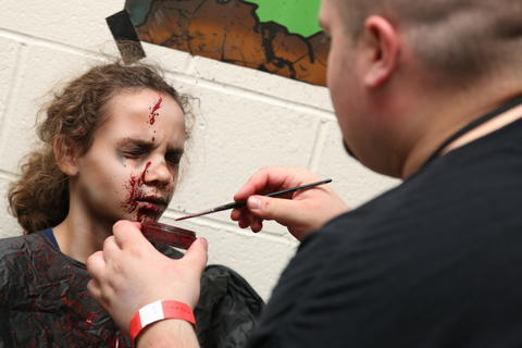 Alyssa Rodriquez, 10, of the Broad Brook section of East Windsor gets the finishing touches of her zombie face applied by Kyle Pasciutti, owner of Decimated Designs, during Hartford Comic Con Saturday afternoon at the XL Center.
