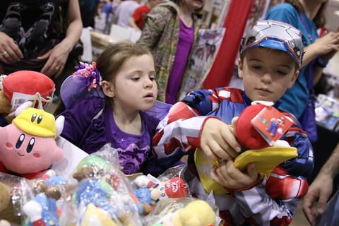 Jaiden Woods, 8, of Newington, dressed as the Iron Patriot, looks through a pile of plush animals with his sister, Danika, 5, Saturday afternoon at Hartford Comic Con held at the XL Center.