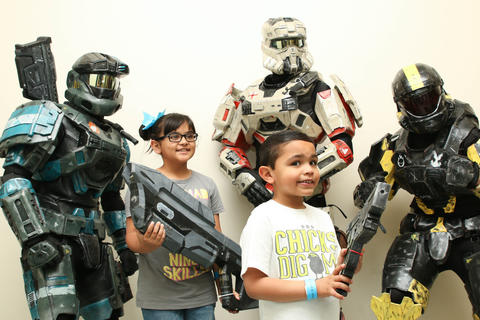Reina Pagan, 9 and her brother, Javier, 6, of Meriden pose for a picture at the Hartford Comic Con Saturday at the XL Center with Spartans Vincent Caputo, Eric Pescetta and Nick Presuto, left to right, all of Ludlow, Mass. Caputo, Pescetta, and Presuto spent more than 400 hours constructing the Halo: Reach armor out of EVA foam.