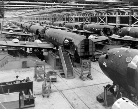 The assembly line in the Douglas Aircraft plant in Park Ridge, Ill., where wings are attached to the fuselage of big C-54 cargo planes. The plant was 15 percent ahead of schedule in June 1944.