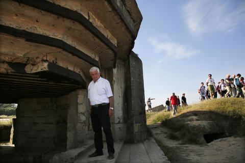 An Italian tourist views a bunker at a strategic site overlooking the D-Day beaches which had been captured by U.S. Army Rangers at Pointe du Hoc, France, August 22, 2013.