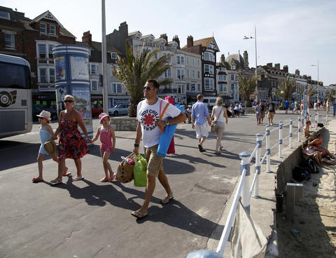 Tourists walk along the beach-front in the Dorset holiday town of Weymouth, England, July 13, 2013. The port was the departure point for thousands of Allied troops who took part in the D-Day landings.