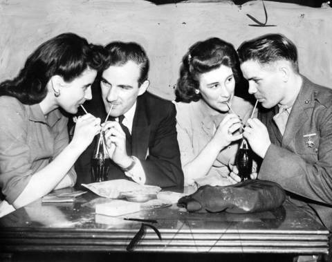 Jean Rose, 18, of Chicago, from left, Chief Petty Officer William Murphy, of Chicago, Phyllis Lurie, 18, of Chicago, and Jack Hooper, a Marine from Evansville, Indiana, enjoy soft drinks together at the Chicago Servicemen's Center. The Center was launched in August of 1941 by the Chicago Commission on National Defense through Mayor Edward J. Kelly. Editors note: This photo has a painted background.