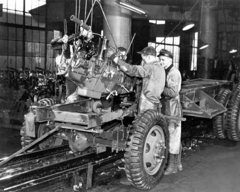 Workmen mount an engine to an Army truck near the end of the assembly line at The Studebaker Corporation in February 1942.