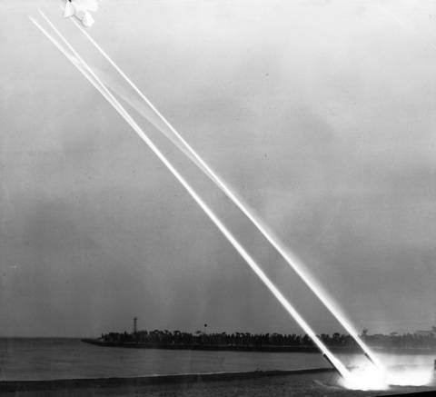 Rockets soar over Lake Michigan at night during a demonstration put on as a war bond drive by the Navy at Foster Avenue Beach in Chicago.