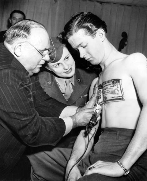 Paul Hensen tattoos the image of a war bond on the chest of Martin E. Rook while WAC Pvt. Gwendolyn Cherry, of South Bend, Ind., watches, circa April 16, 1945.