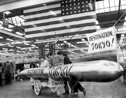 Pat Lambert, left, and Hariette Blumberg, right, watch Keith Carrigan, middle, put the finishing touches on a submarine torpedo he helped build in a Chicago arms plant in 1944. Carrigan, formerly a fireman in the Navy, was discharged after receiving a Purple Heart award and a Presidential Citation.