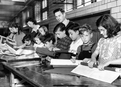 Children work under the supervision of instructor Blanche Kosner and park supervisor Andy Kovach, at the task of making fake bombs made out of newspapers and crepe paper in May 1943 for a simulated air raid in Chicago.
