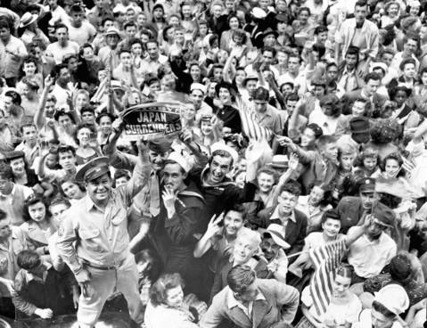 A joyous crowd celebrates the end of World War II at State and Madison Streets in Chicago. Some 500,000 people jammed the Loop streets. Servicemen hold a copy of the Chicago Herald and American.