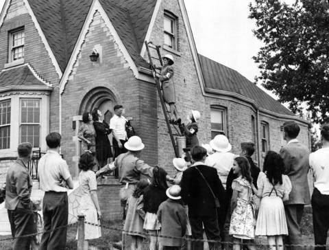 Air Raid Warden Genevieve Hennings, perches on a ladder at in the 5000 block of W. Newport Avenue, where a make-believe incendiary bomb has struck the residence. It was part of an air raid test for Chicago.