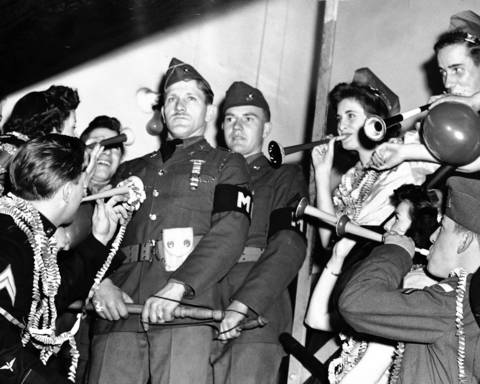 Military policemen A. W. Terbush, center left, and John Meyers, keep their focus amid New Year's revelers at the Chicago Service Men's Center.