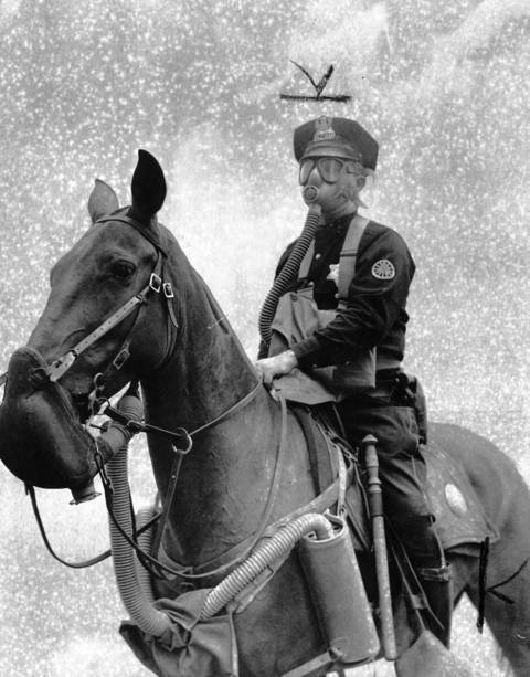 Chicago Police Officer Sullivan calmly rides his horse through a heavy smoke screen on State Street as the Chemical Warfare Service set up a simulated gas attack scene to test and show off their new masks designed to protect both men and horses. Crowds lined curbs to watch the demonstration staged to stimulate war bond sales.