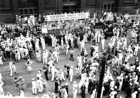 Soldiers and sailors from the Service Men's Center dance with women on LaSalle Street, between Washington and Randolph Streets, in Chicago.
