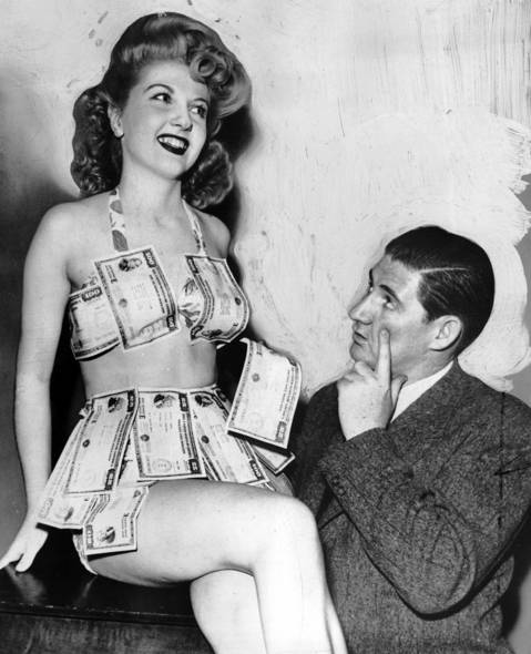 """The Tribune caption for this 1944 posed photograph read that Marge Kucinsky of Chicago """"should be able to keep warm with all those war bonds."""" Pat Buttram, right, was the designer of the costume to promote the sale of bonds to help the U.S. fund World War II. Editors note: this image has a painted background."""
