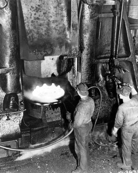 Hammers, striking a blow of 56,000 tons, are being used at Chrysler Corporations Dodge Chicago Aircraft Engine Plant to forge crankcase sections for the huge B-29 engines on Oct. 20, 1944. Shown above is the bottom part of a forge hammer forming one of these crankcases. Expert workmen control the force by a small foot pedal. The crankcases are then assembled into an 18 cylinder, 2200 horsepower, Wright air-cooled radial engine.