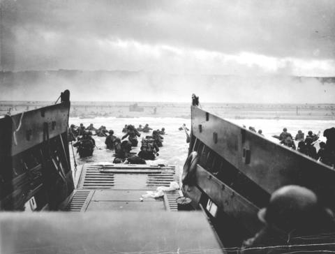 U.S. troops wade ashore from a Coast Guard landing craft at Omaha Beach during the Normandy D-Day landings near Vierville sur Mer, France, on June 6, 1944.