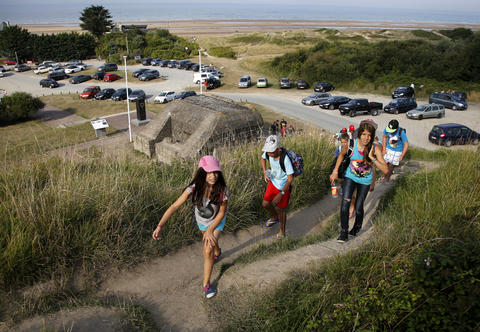 Youths hike up a hill past an old German bunker overlooking the former D-Day landing zone of Omaha Beach near Colleville sur Mer, France, August 23, 2013.