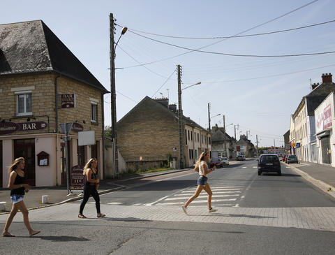 Girls run across the street at the junction of Rue Holgate and RN13 in the Normandy town of Carentan, France, June 21, 2013.