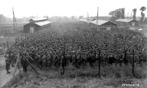 German prisoners of war captured after the D-Day landings in Normandy are guarded by U.S. troops at a camp in Nonant-le-Pin, France, August 21, 1944.