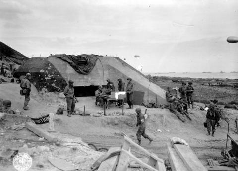 U.S. Army troops congregate around a signal post used by engineers on the site of a captured German bunker overlooking Omaha Beach after the D-Day landings near Saint Laurent sur Mer June 7, 1944.