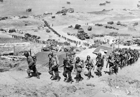 U.S. Army reinforcements march up a hill past a German bunker overlooking Omaha Beach after the D-Day landings near Colleville sur Mer, France, June 18, 1944.
