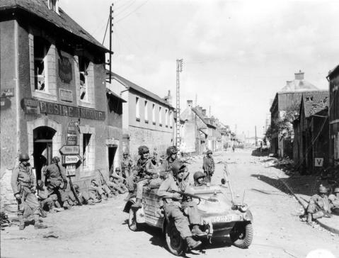 U.S. Army paratroopers of the 101st Airborne Division drive a captured German Kubelwagen on D-Day at the junction of Rue Holgate and RN13 in Carentan, France, June 6, 1944.
