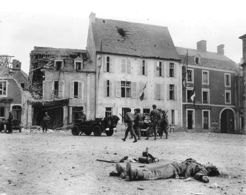 The body of a dead German soldier lies in the main square of Place Du Marche after the town was taken by U.S. troops who landed at nearby Omaha Beach in Trevieres, France, June 15, 1944.
