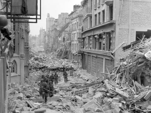 Canadian troops patrol along the destroyed Rue Saint-Pierre after German forces were dislodged from Caen in July 1944. British and Canadian troops battled reinforced German troops holding the area around Caen for about two months following the D-Day landings in Normandy.