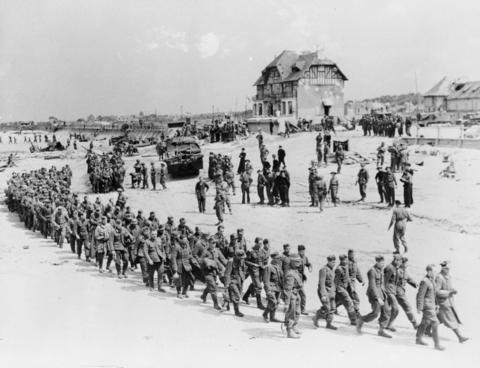 German prisoners-of-war march along Juno Beach landing area to a ship taking them to England, after they were captured by Canadian troops at Bernieres Sur Mer, France on June 6, 1944.