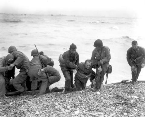 Members of an American landing party assist troops whose landing craft was sunk by enemy fire off Omaha beach, near Colleville sur Mer, France June 6, 1944.