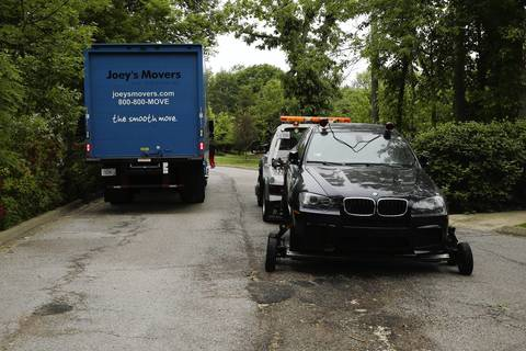 "A BMW sedan is towed from the home of rapper Keith Cozart, or ""Chief Keef,"" as the rapper vacates his rented Highland Park home."