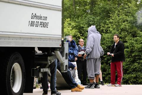 "A Lake County Sheriff's deputy, center, arrives at the rented home of rapper Keith Cozart, or ""Chief Keef,"" to enforce an eviction, keeping occupants and friends of the rapper outside during a search of the home."