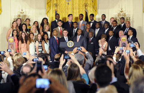 Moments before President Barack Obama entered the room, guests at a ceremony to honor the NCAA Champion UConn men's and women's basketball teams photograph the teams with their cell phones in the East Room at the White House.
