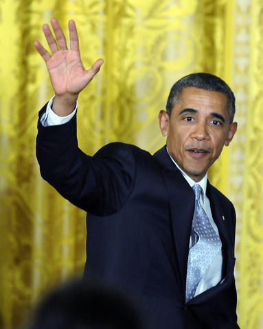 President Barack Obama waves goodbye to the crowd as he leaves the East Room after the UConn ceremony.