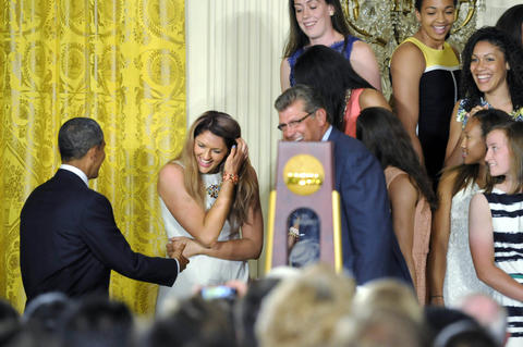 Stefanie Dolson reacts with embarrassment as President Barack Obama checks on her well being after she fell off the riser during a ceremony at the White House.