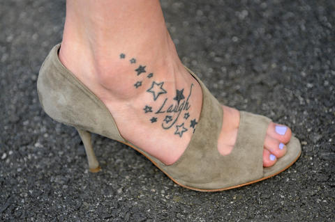 "A tattoo that reads ""laugh"" adorns Stefanie Dolson's right foot, a motto that came in handy after she fell off a riser as President Barack Obama honored the NCAA Champion UConn men's and women's basketball teams at the White House Monday. Dolson was not hurt in the fall - she landed on her feet, in spite of wearing suede stilettos - and laughed about it afterwards."