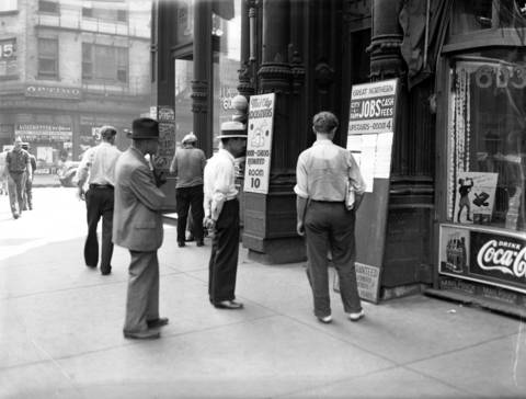 Men look over a jobs board at the Great Northern Employment Bureau at 601 W. Madison Street on July 30, 1937.