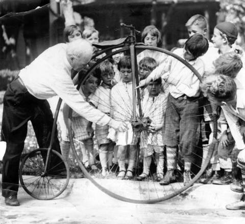 Hubert K. Oram, of 213 N. Menard in the Austin neighborhood, shows off his old fashioned bike on July 3, 1928, to neighborhood children.