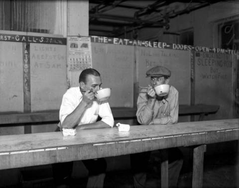 Two men eat cake and coffee at a 10 cent flophouse at 616 W. Adams Street in Chicago, circa Oct. 9, 1931.
