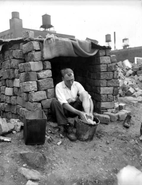 "Wilfred Holmes takes a bath, feet first, in ""hoboland"", circa Aug. 21, 1931."