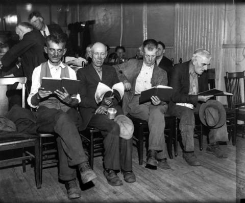 The city's needy read hymnals at the Chicago United Mission, where, after attending services, they are provided with all the coffee and rolls they can consume. Photo taken circa Oct. 6, 1931.